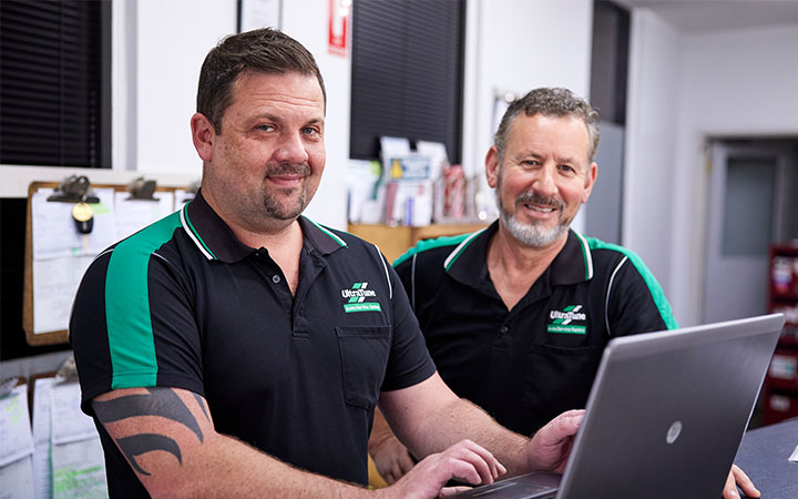 Two men in front of laptop